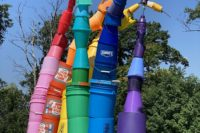 A photo of a rainbow sculpture made of plastic paint buckets.